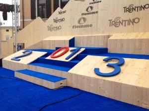 Cavalese Mondiali 2013 palco premiazioni piazza dei Campioni by Claudio Delvai p 300x224 I Mondiali di Fiemme in NUMERI. The NUMBERS of Nordic World Ski Championships Fiemme 2013 (ita eng)